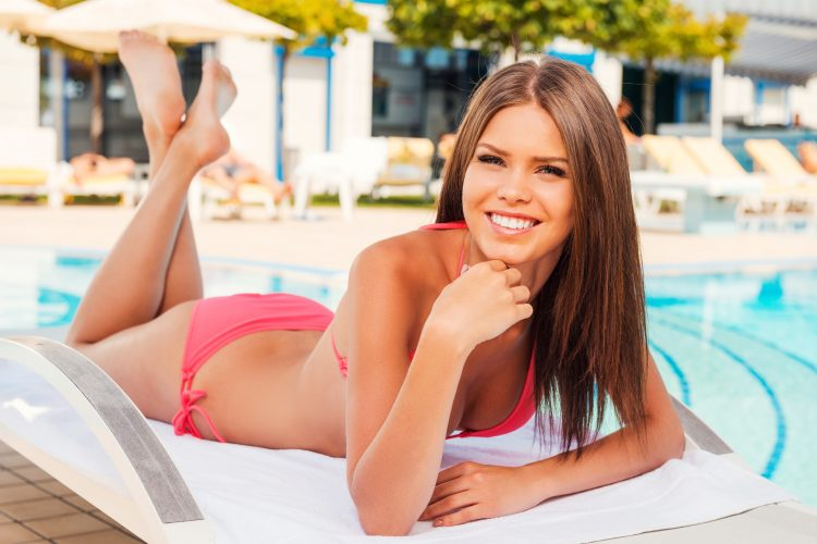 Poolside relaxation. Beautiful young woman in bikini holding hand on chin and smiling while lying on the deck chair by the pool