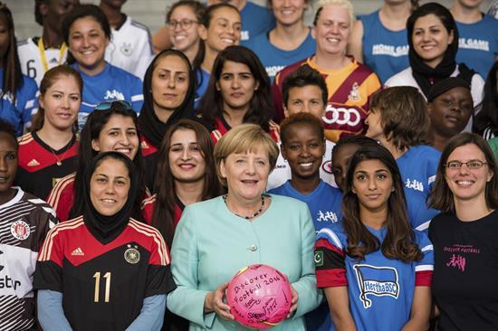 Angela Merkel rindiendo homenaje a mujeres deportistas destacadas en los Olímpicos.