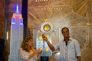 El exjugador del FC Barcelona, Ronaldinho Gaúcho (d), sonríe junto a la directora de comunicación de Unicef, Paloma Escudero (i), mientras enciende,las luces del edificio Empire State que se vistió con los colores del FC Barcelona en Nueva York (Estados Unidos). Autoridades y jugadores del equipo español de fútbol se encuentran en la ciudad con motivo de la inauguración de su nueva oficina. La iluminación del edificio hace parte de un reconocimiento al club y a su fundación, por su alianza con Unicef en el año de su décimo aniversario, informó el club español. EFE/Miguel Rajmil