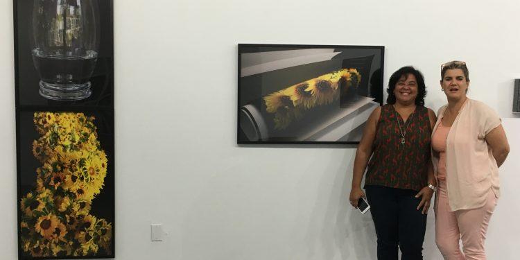 Marilyn Sampera posa junto a la más reciente exposición organizada por ella. (Foto cortesía).