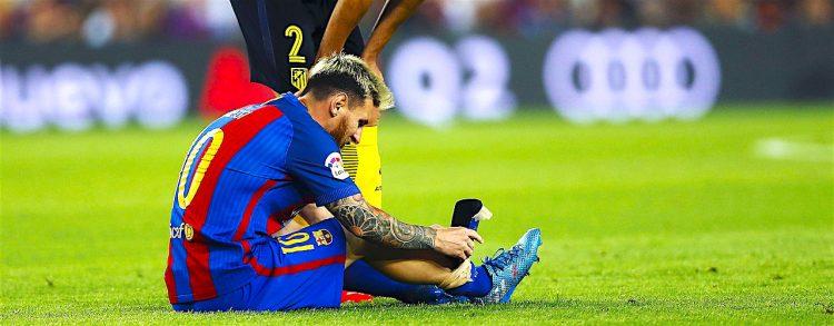 El defensa uruguayo del Atlético de Madrid, Diego Godín (arriba), se interesa por el delantero argentino del F. C. Barcelona, Leo Messi, tras caer lesionado durante el encuentro correspondiente a la quinta jornada de primera división, que han disputado esta noche en el estadio del Camp Nou, en Barcelona. EFE / Alejandro Garcia.