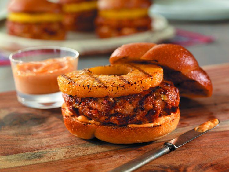 Sirve estas hamburguesas con una fresca ensalada caribeña de tomates y pepinos marinados con trozos de aguacate en vinagreta de lima. (PorkTeInspira.com)
