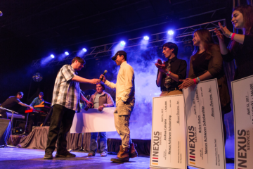Mike Donovan, CEO y presidente de Nexus Services, presenta a los ganadores de la beca Nexus con cheques antes de que Nate Ruess suba al escenario en un concierto comunitario en Verona, Virginia.