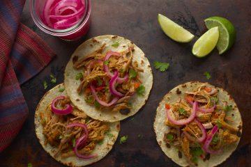 Para servir en tacos, simplemente coloque la carne de cerdo desmechada en mini tortillas de maíz calientes y cubra con las cebollas encurtidas y el cilantro. (Cortesía GOYA)