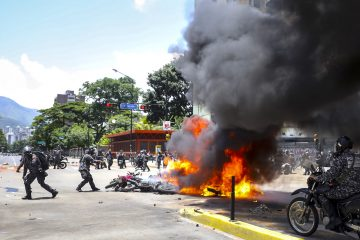 Agentes de la Guardia Nacional Bolivariana lanzan motocicletas usadas por periodistas a un incendio causado por una explosión el pasado, domingo 30 de julio de 2017, en inmediaciones de la Plaza Altamira de Caracas (Venezuela). Un agente resultó hoy herido tras la explosión de dos motos de la Policía Nacional Bolivariana (PNB) y otra de un civil, en las inmediaciones de una protesta ciudadana en Caracas contra las elecciones a la Asamblea Nacional Constituyente, convocada por el presidente venezolano, Nicolás Maduro. EFE/Miguel Gutiérrez