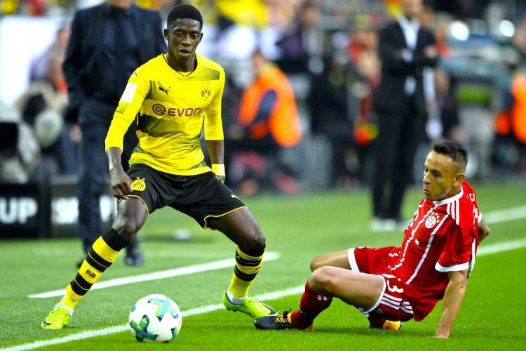 Dortmund's Ousmane Dembele (L) en acción cotta el jugador Rafinha (R) de Bayern's. EFE/EPA/FRIEDEMANN