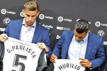 Las dos nuevas incorporaciones del Valencia CF, el defensa brasileño Gabriel Paulista (i), y el central colombiano Jeison Murillo, observan sus nuevas camisetas durante la rueda de prensa de presentación celebrada este mediodía en la Ciudad Deportiva de Paterna (Valencia). EFE/Manuel Bruque