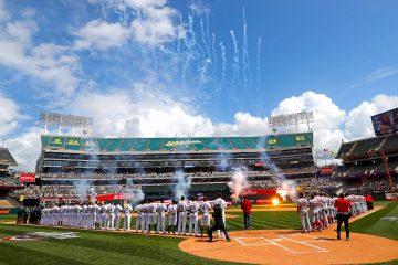 Los Angelinos de Los Ángeles y los Atléticos de Oakland cantan el himno nacional este jueves en el Oakland Coliseum en Oakland, California (EE.UU.). EFE