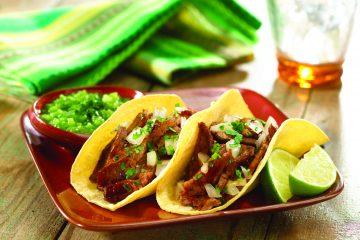 Corta el bistec y sirvelo en las tortillas con cebolla picada, cilantro, y rodajas de limón verde.