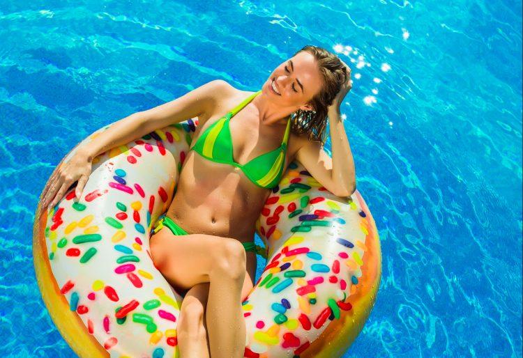 Summer Vacation. Enjoying suntan Woman in bikini on the inflatab