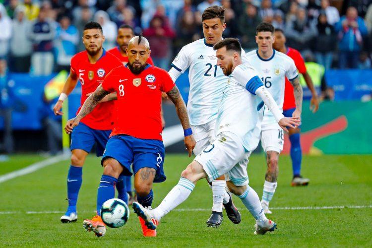 El jugador de Argentina Lionel Messi (i) disputa el balón con Arturo Vidal de Chile, durante el partido Argentina-Chile por el tercer puesto de la Copa América de Fútbol 2019, en el Estadio Arena Corinthians de São Paulo, Brasil, en fecha del 6 de julio de 2019. EFE/Sebastião Moreira