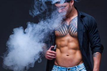 Vaper. The man dressed blue jeans, black shirt and black baseball cap with tattoos smoke an electronic cigarette on the dark background.