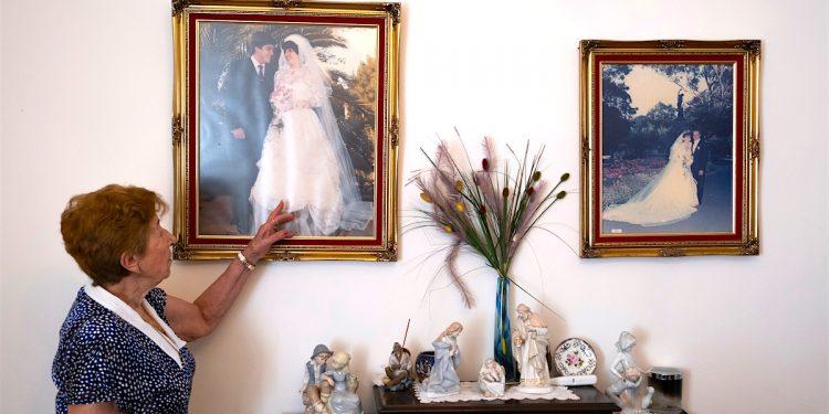 """Leontina García Calzón oserva fotos de sus hijos, es una de las tres españolas que llegaron a Australia en la década de 1960 para trabajar en el servicio doméstico como parte del programa migratorio Plan Marta, se reúnen con otras compatriotas en el Parque Centennial, de Sídney. Más de 700 españolas viajaron a Australia en la década de los 60 mediante un acuerdo de migración asistida: el """"Plan Marta"""" les ofrecía un billete de avión para que trabajasen como empleadas domésticas, aunque en realidad encubría la intención de que esas jóvenes solteras formaran una familia y echaran raíces en un país que necesitaba con urgencia aumentar su población. -EFE/Alisa Yuldybaeva"""