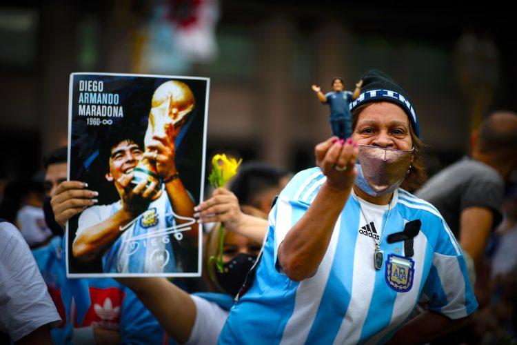 Fotografía de archivo de seguidores de Diego Armando Maradona sosteniendo imágenes de Maradona afuera de la Casa Rosada donde se realizó la capilla ardiente del astro argentino el 26 de noviembre de 2020 en Buenos Aires (Argentina).  EFE/Juan Ignacio Roncoroni