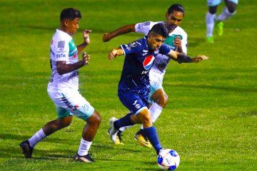 Matias Galvaliz (c) del Motagua es marcado por Bryan Martínez (i) y Richard Nuñez (d) del Platense hoy, jueves 17 de diciembre de 2020, durante el partido de ida de repechaje por el campeonato de la Liga Nacional de Honduras disputado en el Estadio Excelsior de Puerto Cortés (Honduras). EFE