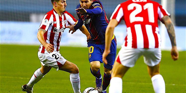 El delantero argentino del FC Barcelona, Leo Messi (c), intenta llevarse el balón ante el centrocampista del Ahtletic, Unai Vencedor, durante el encuentro correspondiente a la final de la Supercopa de España que disputan hoy Domingo en el estadio de la Cartuja de Sevilla. EFE