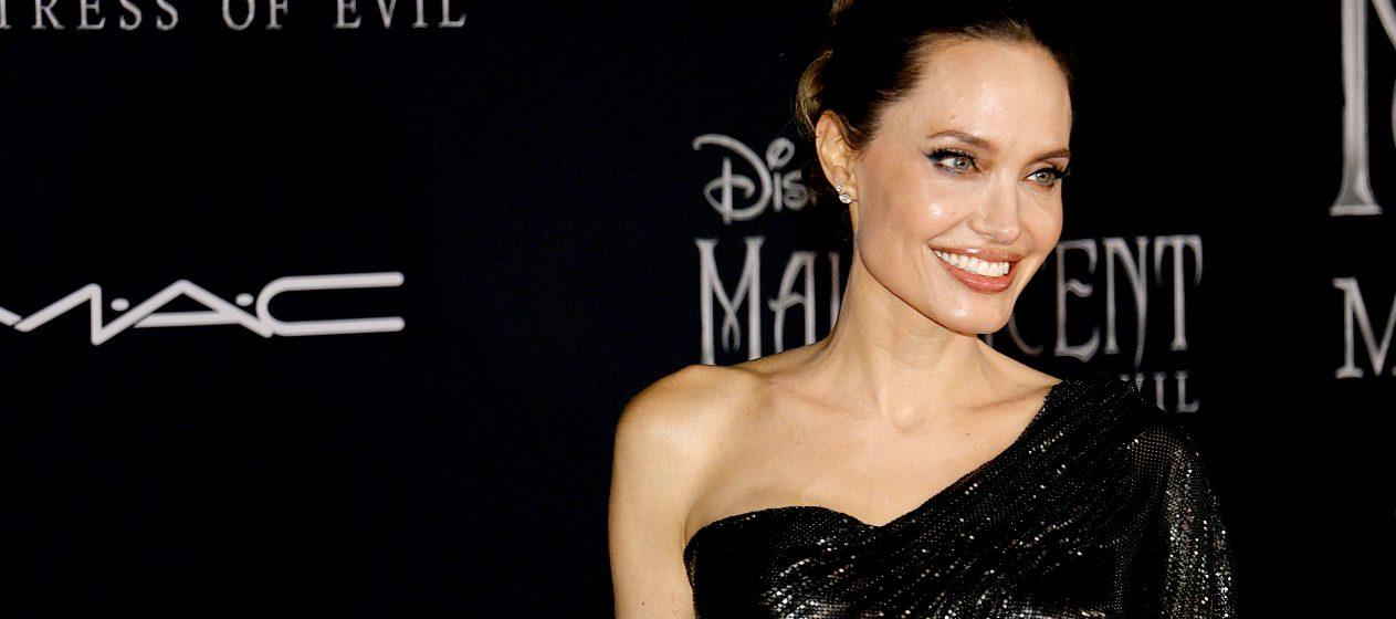 Jolie, que usaba una gabardina larga crema, un bolso Louis Vuitton y sandalias del mismo color y en la mano la botella de vino Peter Michael, llegó sola, sin siquiera un guardaespaldas. (Dreamstime)
